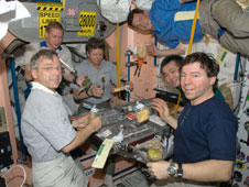 ISS020-E-005082: Expedition 20 crew members share a meal