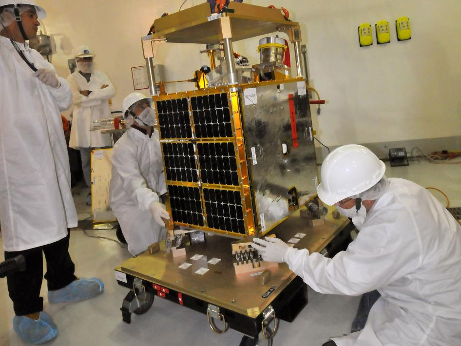Technicians lift the Fast, Affordable, Science and Technology Satellite (FASTSAT-HSV01) from its shipping container.