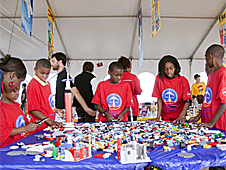 Five students in red t-shirts build space vehicles using LEGO building blocks