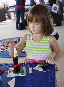 Little girl building a space ship using LEGO building blocks