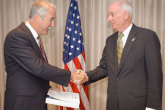 Admiral Gehman hands Columbia Accident Investigation Report to NASA Administrator Sean O'Keefe.