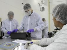 From left, Charlie Friedericks and Giovanni Manelli, with the NASA's Ames Research Center inspect the Ames-managed O/OREOS nano satellite at Kodiak Launch Complex on Kodiak Island, Alaska, Oct. 17, 2010, in advance of the satellite's planned launch into orbit.