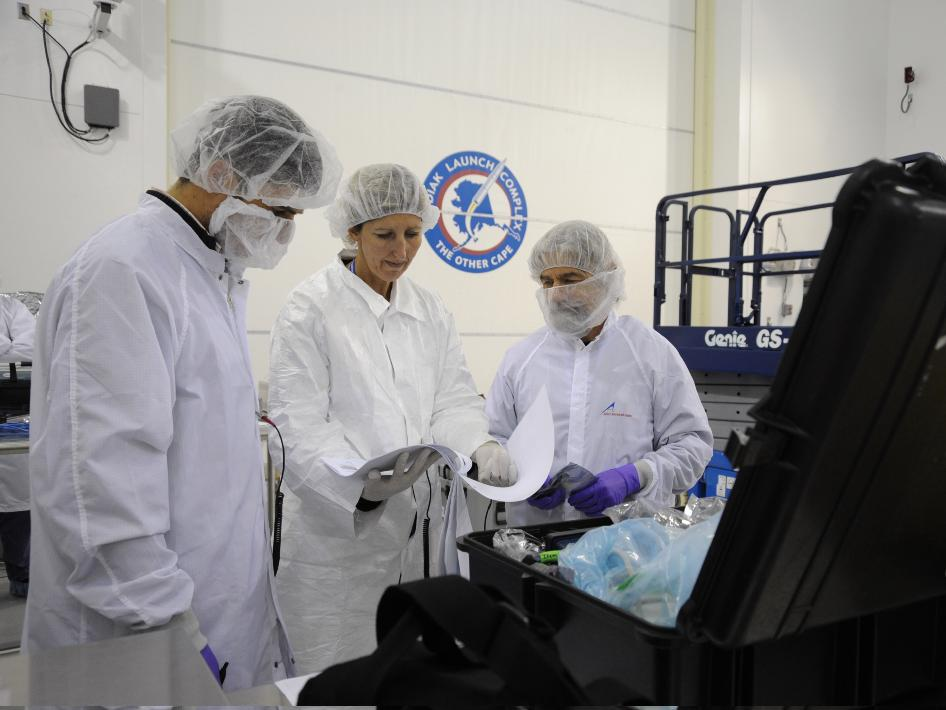 From left, Giovanni Manelli, with the NASA's Ames Research Center; Kitty Sandan, with Aerospace Corp.; and Charlie Friedericks, with Ames, inspect the packing list and instructions for the Ames-managed O/OREOS and NanoSail-D from NASA's Marshall Space Flight Center nano satellites at Kodiak Launch Complex, Alaska, Oct. 18, 2010.