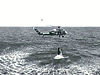 A helicopter pulls a Mercury capsule from the ocean