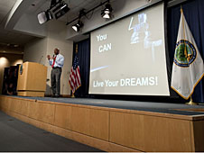 Leland Melvin standing on a stage talking to students