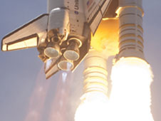 Close-up of space shuttle main engines during launch.