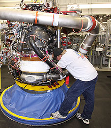 Technician works on space shuttle main engine.