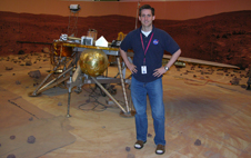 Dr. Brent Bos standing next to a mock-up of the Mars Phoenix Lander