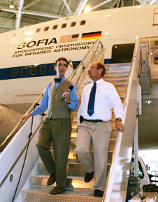 Bill Nye the Science Guy, left, interviews SOFIA program manager Bob Meyer as they walk down the aircraft steps of agency's 747SP flying observatory