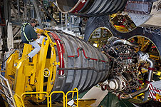An engineer guides an shuttle engine installation.