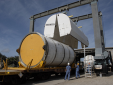 At Kennedy's railroad yard, a protective cover is being placed over a solid rocket booster segment