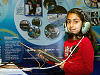 Young girl wearing a headset stands in front of a large poster