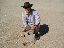 Michael Wing holding a rock in the desert