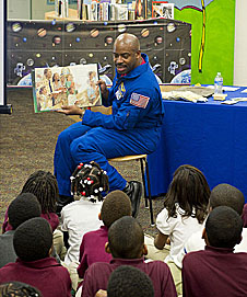 Leland Melvin holds up a book in front of students