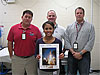 Standing with her mentors, Ariane Callender holds a picture of a space shuttle