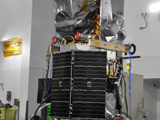 Glory's Aerosol Polarimetery Sensor (APS), under a protective bag here, is the triangular-shaped part of the spacecraft highest from the ground in this photograph.
