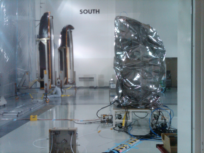 The Glory spacecraft (wrapped in thermal blanketing) and the two Taurus XL fairing halves share space in the launch site payload processing facility.