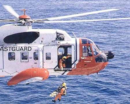 A Coast Guard helicopter rescuing a person stranded in the ocean.