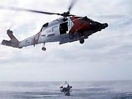 A Coast Guard helicopter performing a rescue in the ocean.