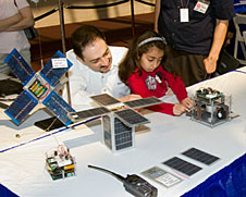 A student examines electronic equipment and spacecraft models