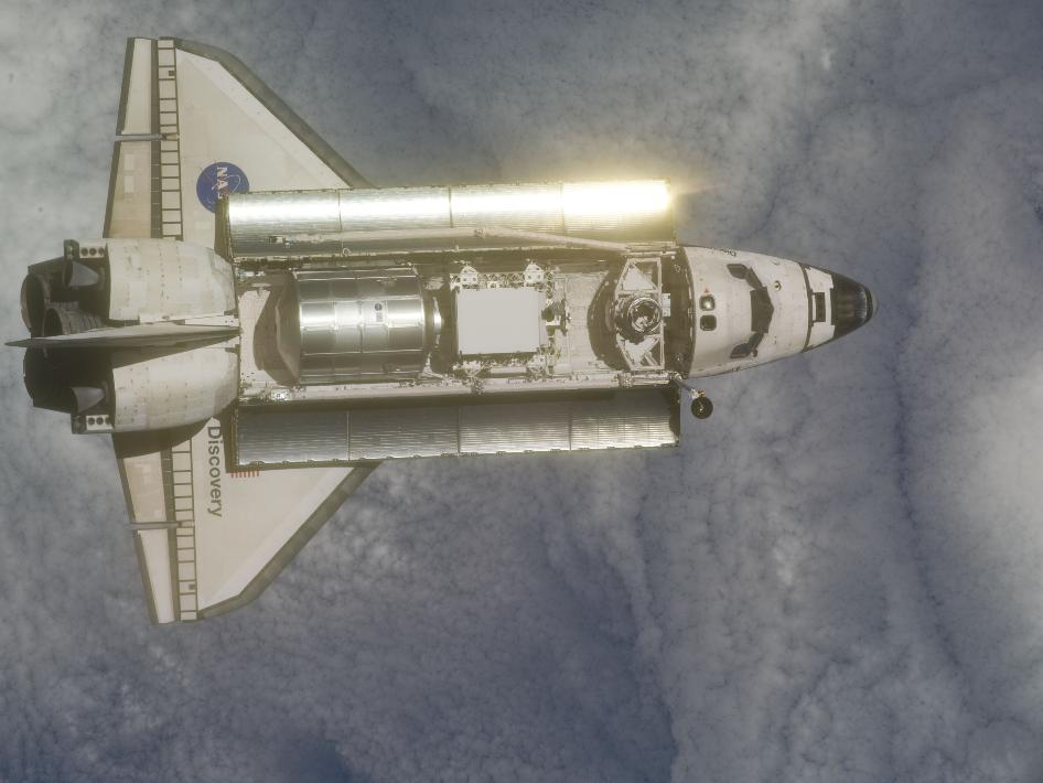 Backdropped by a cloud-covered part of Earth, space shuttle Discovery is featured in this image photographed by an Expedition 26 crew member as the shuttle approaches the International Space Station during STS-133 rendezvous and docking operations. Docking occurred at 2:14 p.m. EST on Feb. 26, 2011.