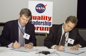 NASA Associate Administrator for Safety and Mission Assurance and his counterpart from the Department of Defense Missile Defense Agency sign the agreement to exchange information on safety issues. Photo credit: NASA JSC/Mike Gentry.