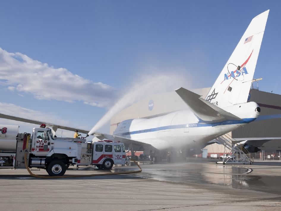 The SOFIA aircraft is bathed by water from Air Force Plant 42 fire department trucks, outside its hangar in an effort to check for leaks around the telescope cavity door.