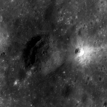 A bright crater on the flank of a larger dark halo crater