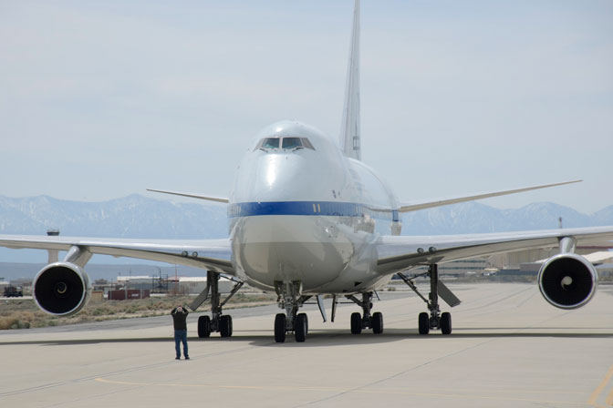 The NASA-DLR Stratospheric Observatory for Infrared Astronomy 747SP dwarfs a ground crewman as it taxis to a stop on the flight line at NASA's Dryden Flight Research Center on Edwards Air Force Base, Calif.