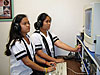 Two students wearing headsets and working at computer consoles