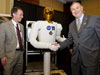 Congressman Dana Rohrabacher shakes hands with Robonaut 2 with NASA Chief Technologist Bobby Braun.