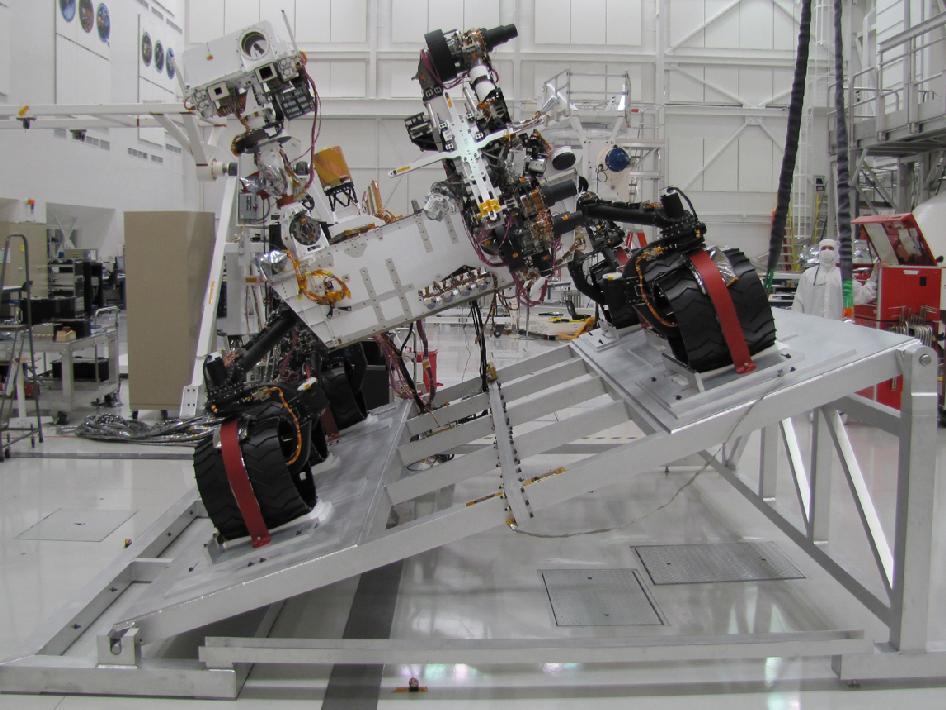 The image shows Curiosity on a tilt table in the Spacecraft Assembly Facility at NASA's Jet Propulsion Laboratory.