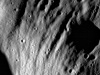Ejecta scours deep grooves into the walls and rim of an unnamed crater
