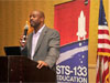 Leland Melvin speaks into a microphone