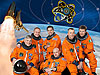 The STS-134 crew poses in orange suits in front of a picture of the shuttle and the mission's patch over Earth