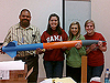 Three team members and their rocketry mentor hold a rocket