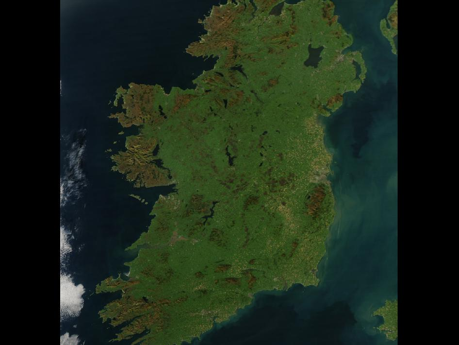 It is easy to see from this true-color image why Ireland is called the Emerald Isle. Intense green vegetation, primarily grassland, covers most of the country except for the exposed rock on mountaintops. Ireland owes its greenness to moderate temperatures and moist air. The Atlantic Ocean, particularly the warm currents in the North Atlantic Drift, gives the country a more temperate climate than most others at the same latitude.