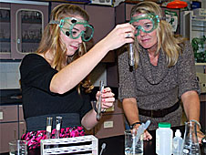 A student observes the results of an experiment while her teacher looks on