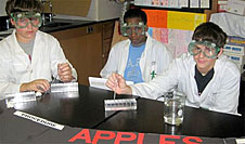 Three students wearing lab coats and goggles with lab equipment