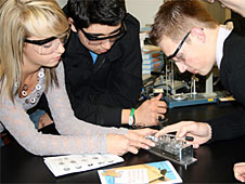 Three students work with lab equipment