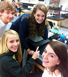 Four smiling students in a laboratory