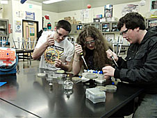 Three students using science lab equipment