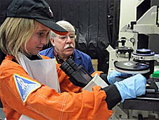 A professor looks on as a student in an orange flight suit works with lab equipment