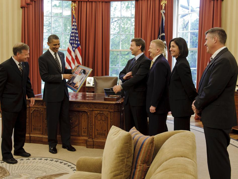 STS-133 commander Steven Lindsey, far left, presents a montage to President Barack Obama as crew members Michael Barratt, pilot Eric Boe, Nicole Slott and Steve Bowen look on during a visit to the Oval Office, Monday, May 9, 2011, in Washington.