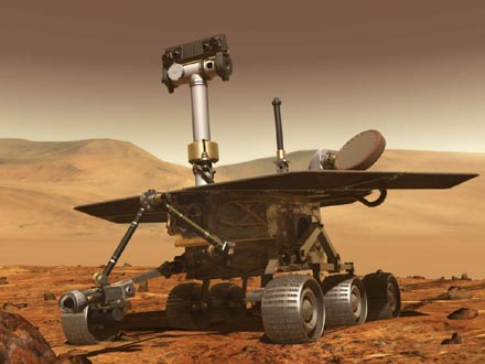 An artist's concept of the Mars rover Spirit approaching an interesting rock.