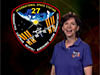 Cady Coleman next to the Expedition 27 mission patch