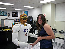 Ashley Allman shaking hands with a humanlike robot