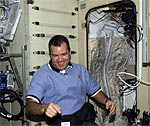 Astronaut Paul Richards is next to a sleep station inside the Zvezda Service Module.