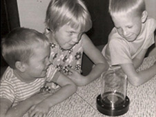 Debra Sea and her brothers, David and William, admire an Apollo 11 moon rock on their kitchen table