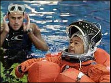 Astronaut attired in a training version of the shuttle launch and entry garment floating in pool at NBL
